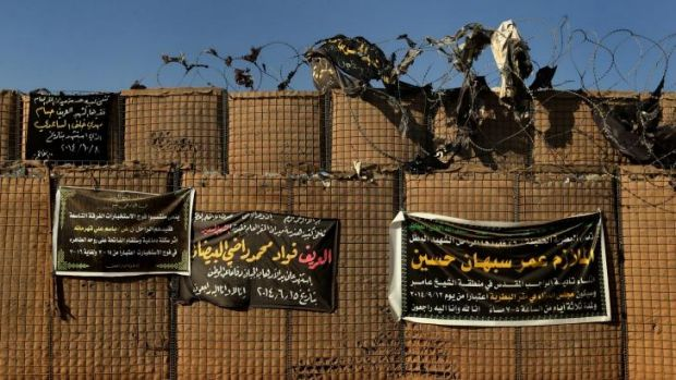 Banners naming the Iraq soldiers that have died in combat line a wall at Camp Taji.
