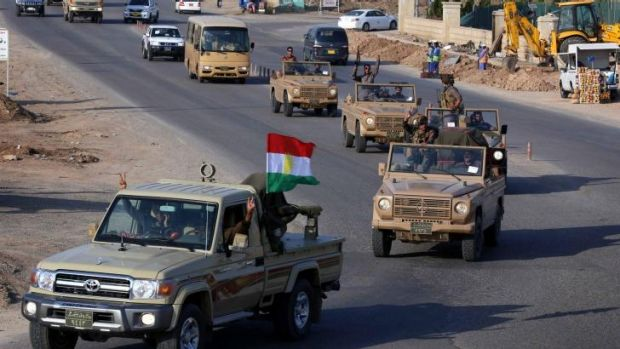 Iraqi Kurdish fighters drive through Erbil in northern Iraq on their way to the border with Turkey and ultimately the ...