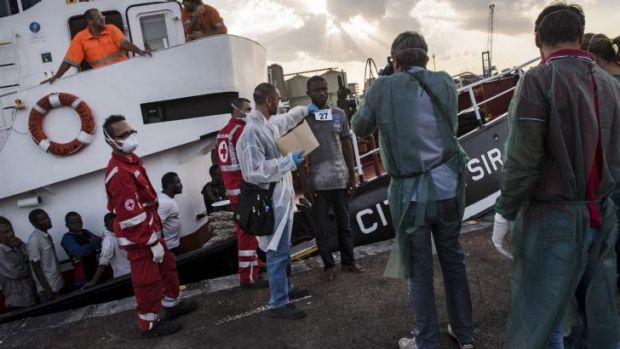 Processing: Refugees from Gambia, Nigeria, Ghana, Bangladesh, Afghanistan and other countries disembark an Italian ...