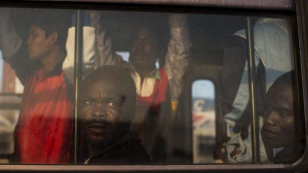 Perilous voyage: Refugees from Nigeria and Ghana wait on a bus to be taken to temporary accommodation after arriving to ...