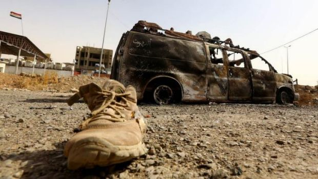 A burnt vehicle belonging to Iraqi security forces at a checkpoint in east Mosul.