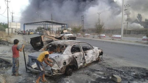 Children stand next to a burnt-out vehicle during clashes between Iraqi security forces and IS militants in Mosul.