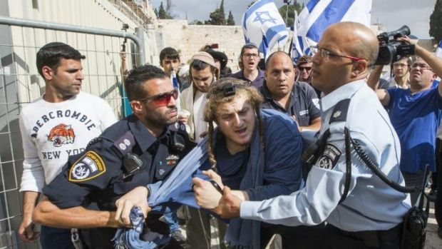 Israeli police wrestle with a far-right religious Jew trying to force his way into the al-Aqsa Mosque compound, sacred ...