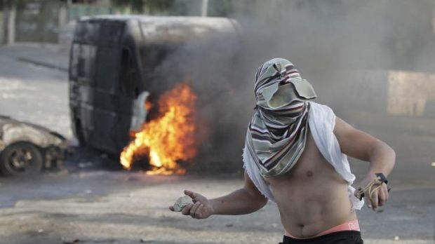 A Palestinian youth throws a rock during clashes with Israeli security forces in occupied East Jerusalem on Thursday.