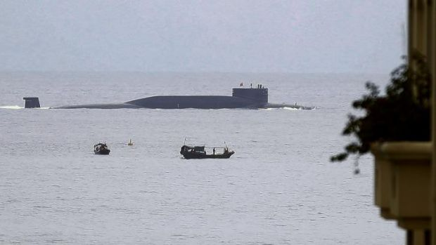 Fishermen look at a Chinese nuclear submarine that sails past Yalong Bay in Sanya, south China's Hainan Province.