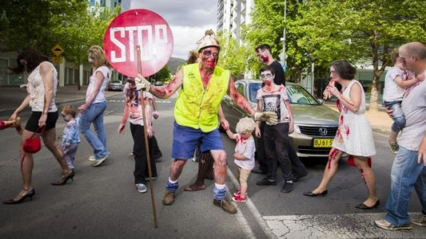 Dead stop: Paul McKie of Downer stops traffic for his fellow zombies in Civic during the annual Canberra Zombie Walk.