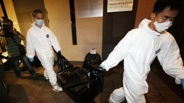 Workers from Hong Kong's Food and Environmental Hygiene Department carry the remains of a woman from the flat following ...