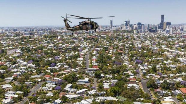 A Black Hawk helicopter flies over Brisbane.