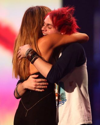 Michael Clifford of 5 Seconds of Summer hugs Delta Goodrem after the band's ARIA win.