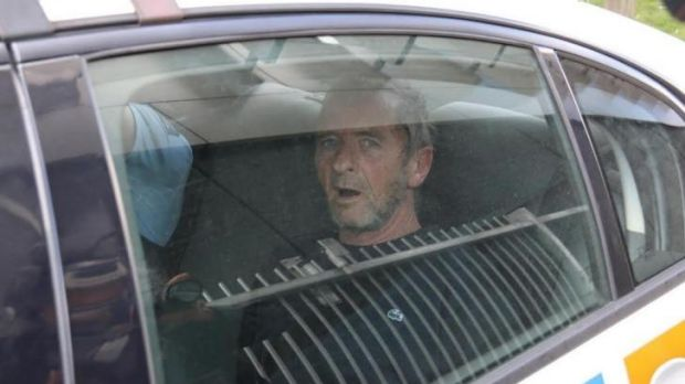 Back in cuffs: AC/DC drummer Phil Rudd is taken away in a police car.