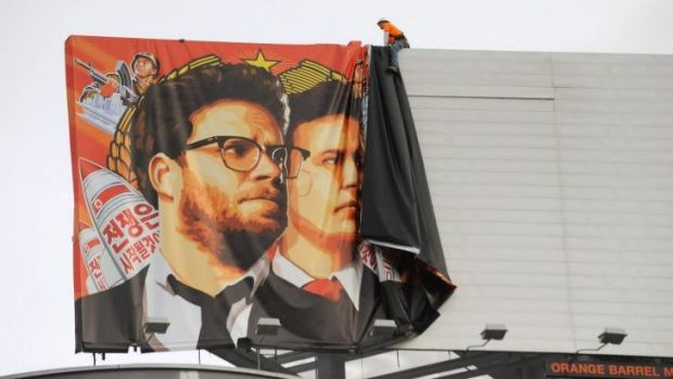 Workers remove a poster for The Interview from a billboard in Hollywood, California, a day after Sony's announcement ...