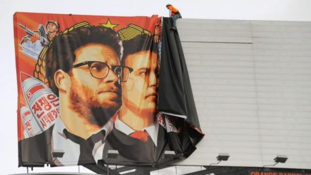 """Workers remove a poster for """"The Interview"""" from a billboard in Hollywood."""