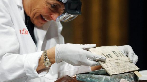 Conservator Pam Hatchfield removes a newspaper from a time capsule, which was placed under a cornerstone of the State ...
