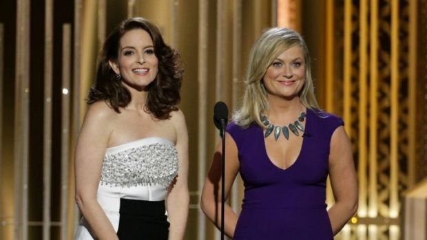 Golden Globes co-hosts Tina Fey, left, and Amy Poehler cracked the Bill Cosby gag to stilted laughter.