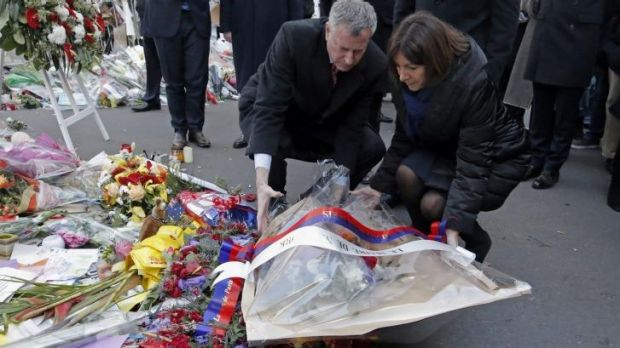 New York City Mayor Bill de Blasio, left, and Paris mayor Anne Hidalgo, right, lay a wreath of flowers at the site of ...