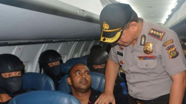 An Indonesian official poses for a photo with Bali Nine ringleader Myuran Sukumara on the flight from Bali to Cilacap.