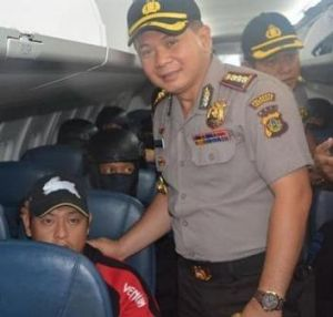 An Indonesian official poses for a photo with Bali Nine ringleader Andrew Chan on the flight from Bali to Cilacap.