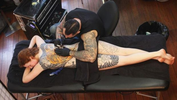 """Going with the flow: Tattooist Kian """"Horisumi"""" Forreal gives Elkie Lewer a full back, neck to knee image of a tiger."""
