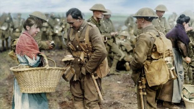 A soldier from the Canterbury Regiment digs deep to buy cakes from a local woman. France, 1917