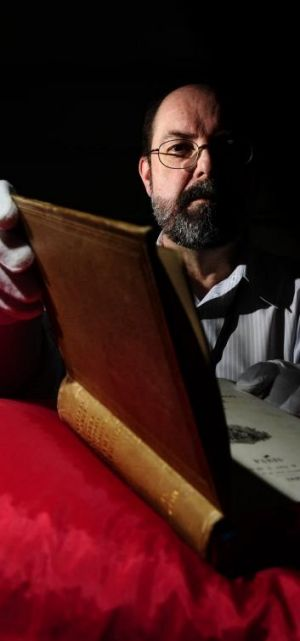 Andrew Sergeant, rare books reference librarian at the Australian National Library, with a book covered in human skin.