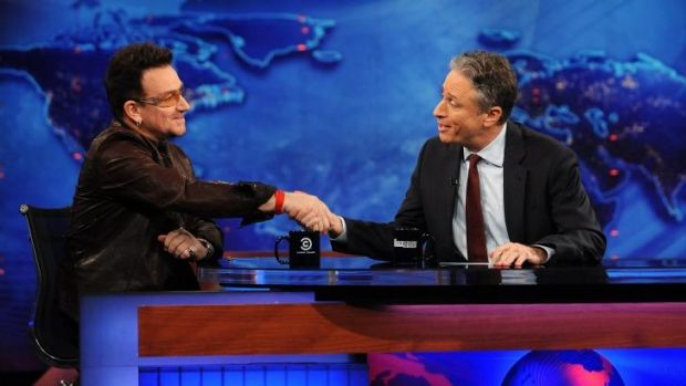 In 2011, U2 frontman Bono, left, shakes hands with host Jon Stewart.