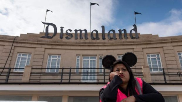 Gloomy ... a steward gets into the spirit of Banksy's new theme park.