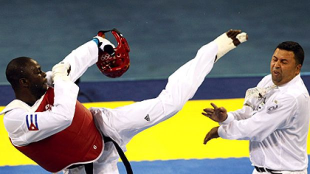 Angel Valodia Matos of Cuba kicks a referee during his bronze medal taekwondo bout.
