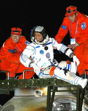 Chinese astronaut Nie Haisheng is helped out of the re-entry capsule of China's second manned spacecraft, Shenzhou VI, ...