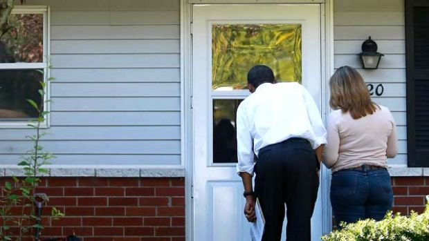 Anyone home? Barack Obama and a campaign volunteer knock on a door in Holland, Ohio.
