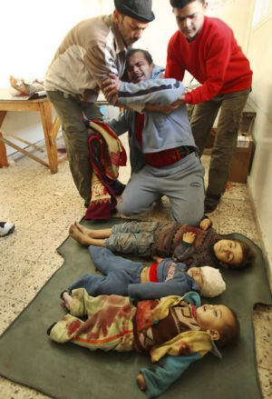 Friends try to comfort a distraught Palestinian over the bodies of three children, one of them his son, at al-Shifa ...