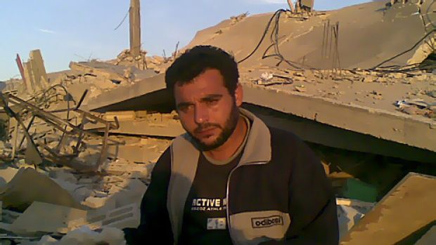 Khalid Abed Rabbo stands by the ruins of his house.