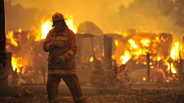 A firefighter stands in the debris as a bushfire rages in the Bunyip area. Picture: Jason South.