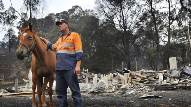Anthony Sexton with his horse, which is burnt,  stands before the smouldering ruins of his home at Koornalla near ...
