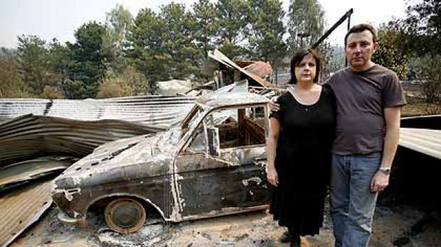 Ian and Annemarie Harris stand in front of the burnt remains of their house, about 10 kms south of Stanley.