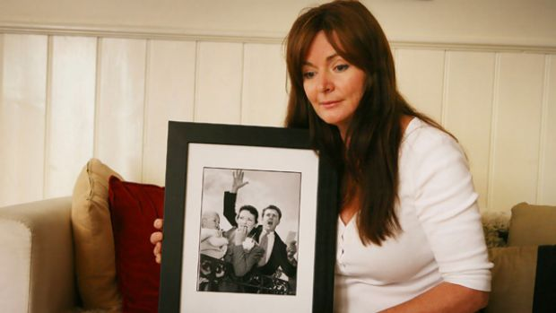 Marisa Robbins holds an old photo of her parents, Lloyd and Mary Martin, who died fighting to save their Humevale home.