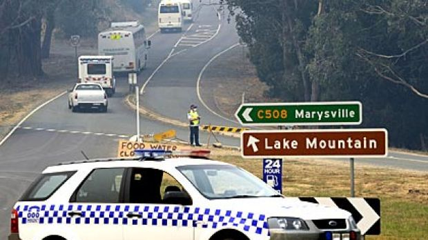 A convoy of buses takes Marysville residents back to their fire-ravaged town.