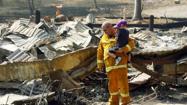 Firefighter Steve Nash with son Lachlan at their burnt house.