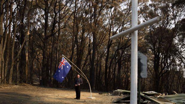 Reverend Stephen Holmes with part of a WW1 plaque saved from the fires. St Peter's Anglican church was built as a ...