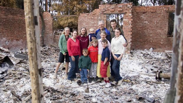 Still smiling, the Lisle family take time out from sifting through the ashes of their home to pose and grin for the cameras.