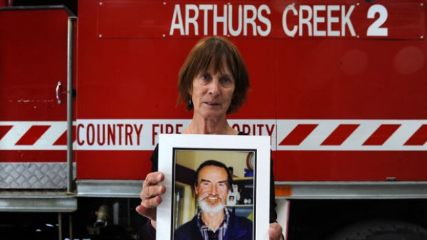 Grieving: Dini Shepherd holds a picture of her husband Joe. The CFA is  investigating whether he died in the line of duty.
