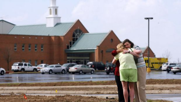 Mourners comfort each other in front of the First Baptist Church in Maryville, Illinois, where a gunman shot dead the ...