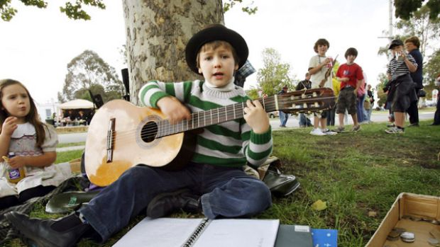 Busker John Bennett, 8, an enthusiastic talent with the ukulele and guitar, works through his song list for an ...
