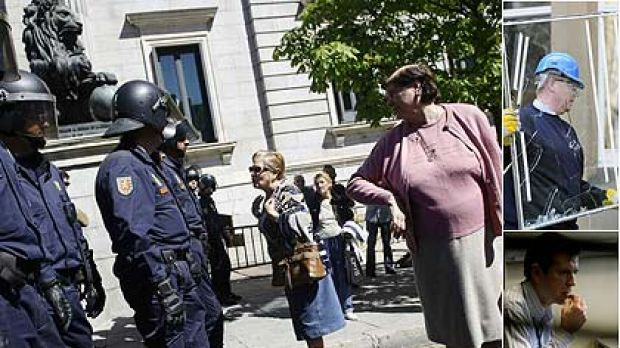 Women confront riot police in an anti-government demonstration by the self-employed and small business owners in Madrid. ...