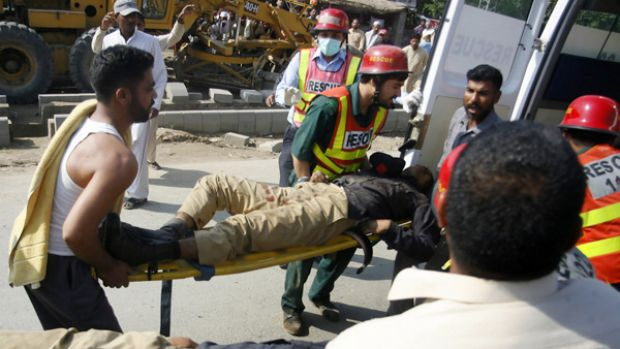 Pakistani police and ambulance officers carry the injured to safety during the attack.
