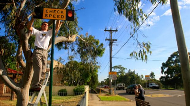 """""""It's not just for the safety of the kids, it's also for fairness on drivers''...Peter Olsen installs a sign near ..."""