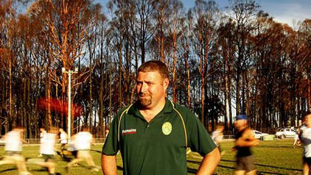 Cameron Caine, President of the Kinglake Football Club, stands on Memorial Oval as players perform training drills on ...