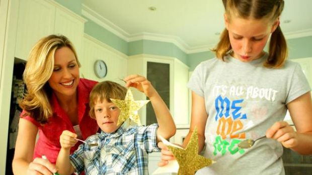 Tara Dennis helps Byron O'Mahony and sister Sarelle make glitter star Christmas ornaments.