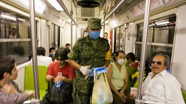 Breathe uneasy . . . a  soldier hands out masks on the metro  in Mexico City. More than 500 events have been cancelled ...