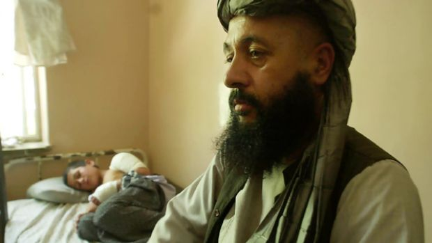 Lawmaker Abdul Khaliq with his injured son, Mohammed Yousaf, 9, at the Kandahar Hospital in southern Afghanistan in July ...