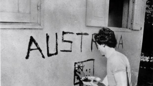 "Just days before his death, Greg Shackleton paints ""Australia"" on a shop wall in Balibo in East Timor in 1975."